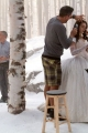 Snow dresser Claire Belisle and prop man Denis Hamel talk while Lily Collins is groomed,